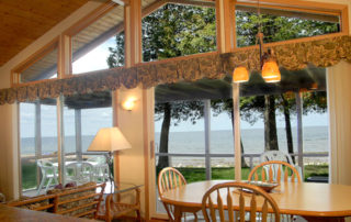 View of the bay through floor to ceiling windows of Shallows Cottage