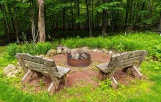 Bluffside's fire pit and rustic wooden benches surrounded by woods